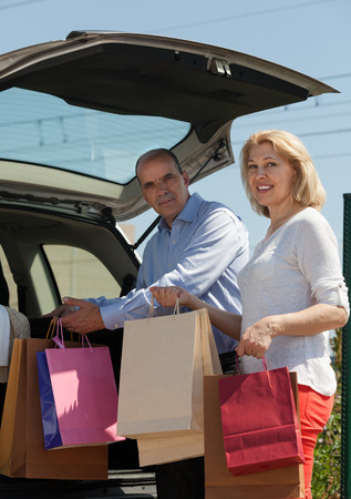 Senior mature couple staying near opened boot with purchases after shopping  photo