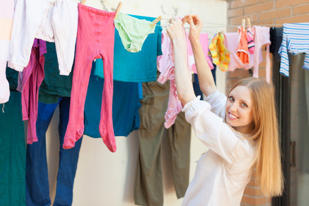 laundry line: Positive long-haired girl drying clothes on clothes-line after laundry Stock Photo