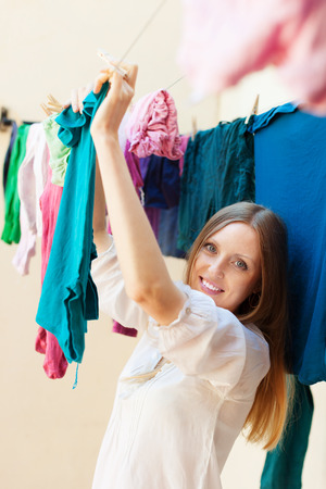 longhaired: Long-haired housewife drying clothes on clothes-line Stock Photo