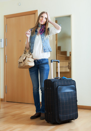 pensive woman with suitcase near door at home