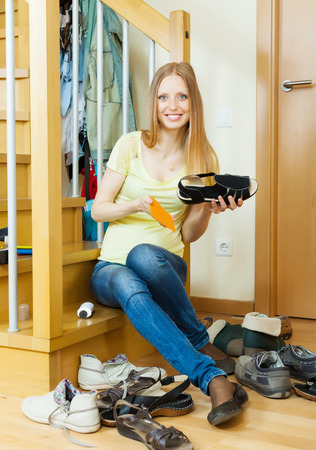 Happy long-haired woman cleaning shoes at home photo