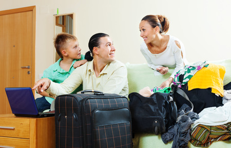 Ordinary family of three with teenager reserving hotel  for vacation photo