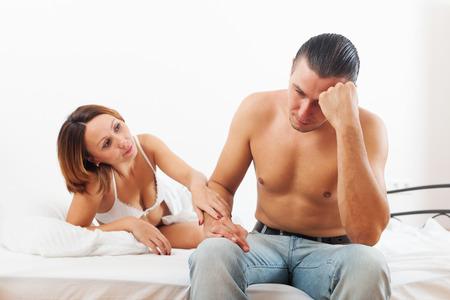 mujer desnuda sentada: El hombre ha triste, mujer consolarlo en el dormitorio Foto de archivo