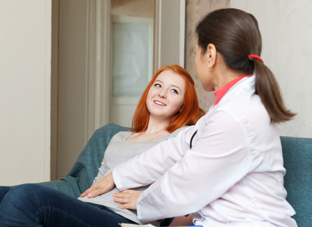 Mature doctor touching  belly of teenager in inter. Focus on patient Stock Photo - 30178904
