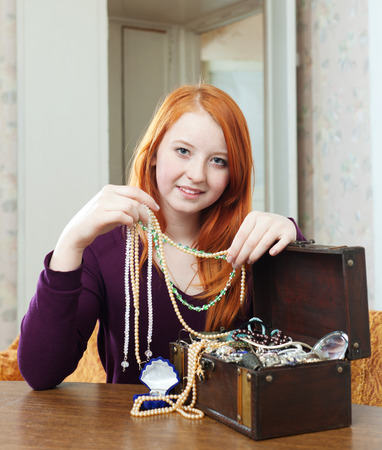 earing: portrait of teen girl chooses jewelry