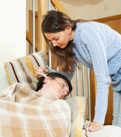 nosotrophy: Girl  dripping eardrops to man  in home Stock Photo