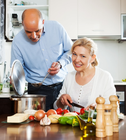 Ordatary mature couple cooking healthy food at home kitchen photo