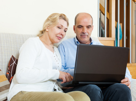 wistful: Wistful mature couple  with laptop in room  Stock Photo