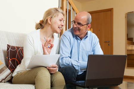Smiling mature couple with documents and laptop in home interior photo