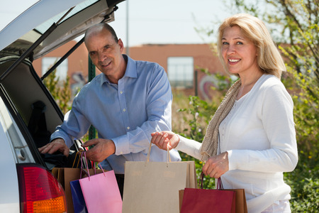 Elderly man and woman putting bags with purchases in car trunk photo