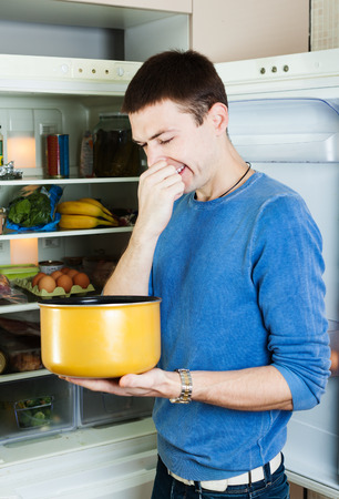 frowy:   man   holding her nose because of bad smell from food near refrigerator  at kitchen