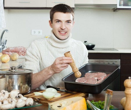 roasting pan: smiling guy cooking  meat with  mushrooms and potatoes. Adding raw meat in roasting pan