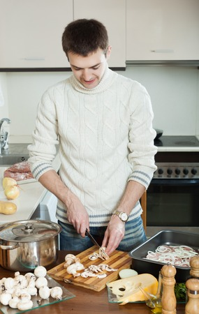 roasting pan: Handsome man cooking  meat with  mushrooms and potatoes. Adding champignons in roasting pan