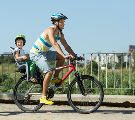 freetime activity: Happy smiling young father on bicycle with child in baby seat behind