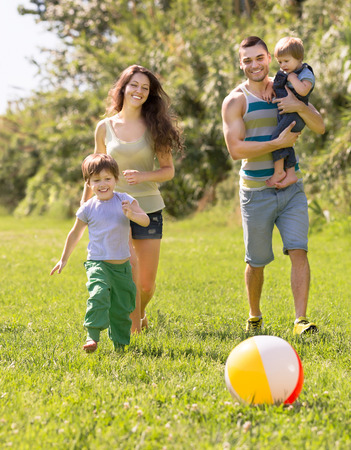 Happy parents with two children spending their free time in the park photo