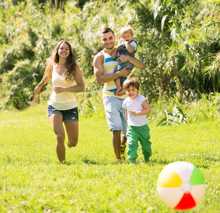 Happy parents with two children playing with ball outdoor photo