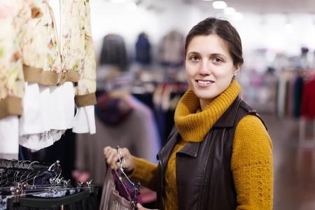 ordinary woman: Ordinary woman choosing skirt at clothing store