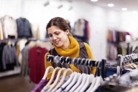 clothing store: Girl choosing casual wear at clothing store