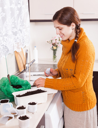 cheerful girl sowing seeds in ground at table in domestic kitchen photo
