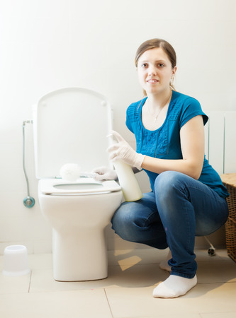 Smiling  woman cleaning toilet brush with sponge and cleaner  photo