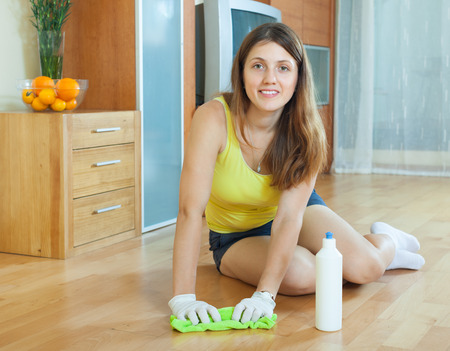 cleanser: Girl rubbing wooden floor with rag and cleanser at home