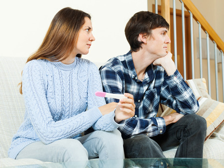 Sad worried woman with pregnancy test with unhappy man photo