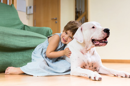 Smiling girl toddler on the floor with dogo Argentino photo
