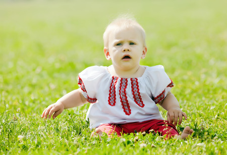 baby in traditional folk clothes on grass photo