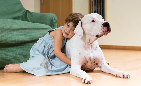 Happy female toddler on the floor with dogo Argentino photo