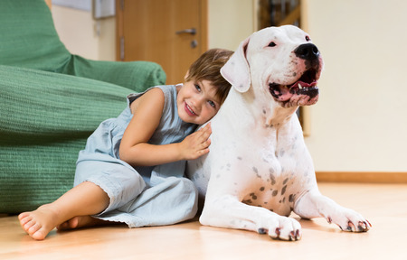 Nice girl toddler on the floor with dogo Argentino photo