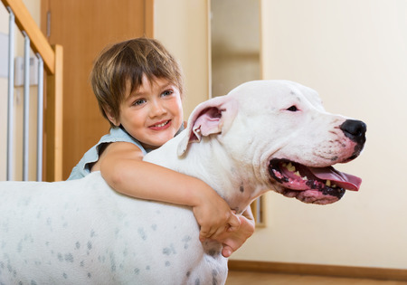 small nice girl on the floor with dogo Argentino (focus on dog)  photo
