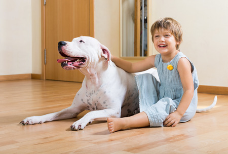 small nice girl on the floor with dogo Argentino  photo