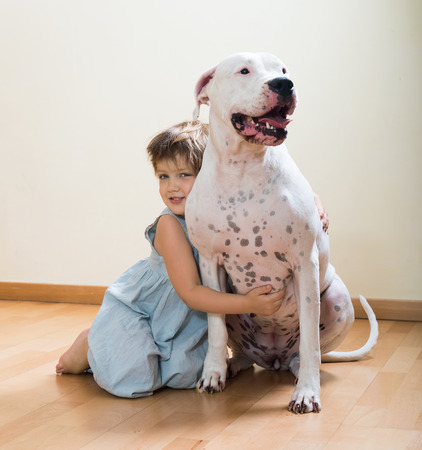 preteen girl on the floor with dogo Argentino(focus on dog) photo