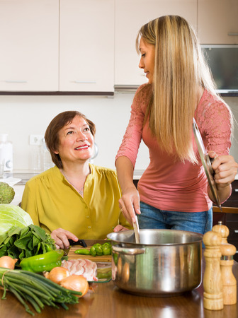 Smiling adult daughter with aged mother cooking dinner at kitchen photo