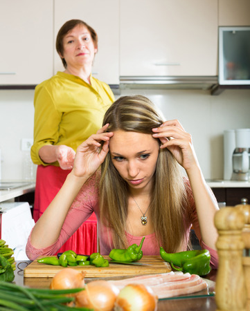 fracas: Family quarrel between adult daughter and elderly mother in the kitchen
