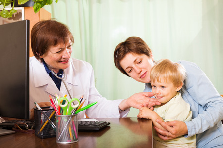 auscultoscope:  pediatrician doctor examing baby at clinic office