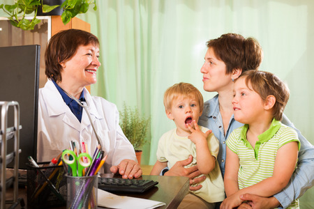 children talking: Young  mother of two children  talking with friendly pediatrician doctor at clinic office