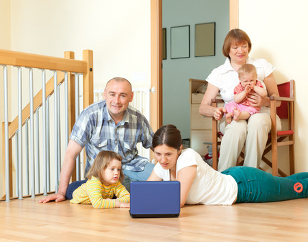 Portrait of happy multigeneration family with laptop on floor at home photo