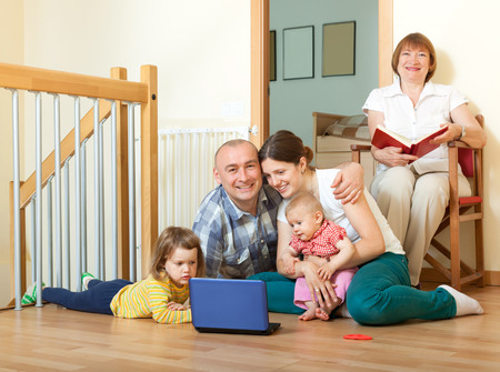 Happy family of three generations using with laptop on floor in home interior  photo