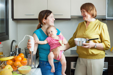three generations of women: Happy women of three generations with blender in domestic kitchen at home