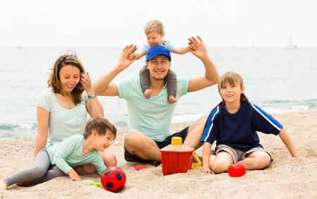 Portrait of smiling parents and their children on  sand by sea photo