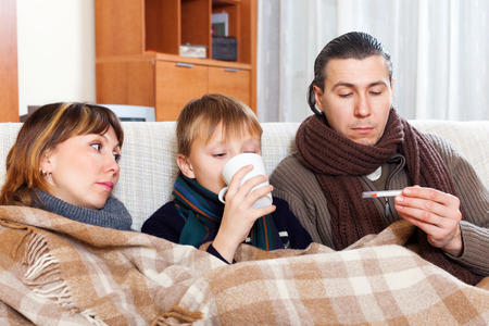 cold woman: Family of three with teenage son are ill at home Stock Photo