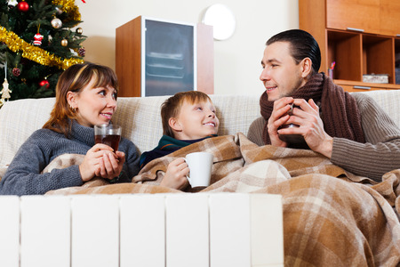 family of three with cups of tea warming near warm radiator in Christmas time at home Stock Photo