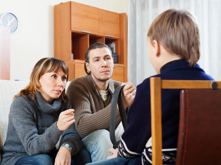 Parents with belt berating teenage son at home photo