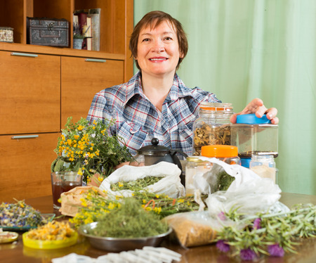 Smiling aged woman with herbs at table in home photo