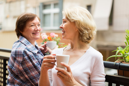 Smiling senior female friends relaxing with cup of coffee on balcony photo
