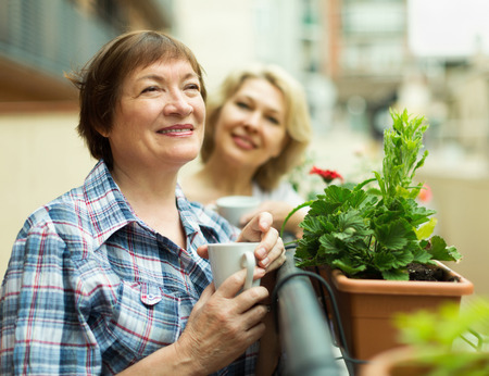 Two  happy pensioner drinking coffee on balcony and smiling photo