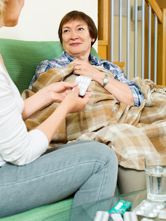 soporific: Mature woman offering medicine and water to pensioner at home