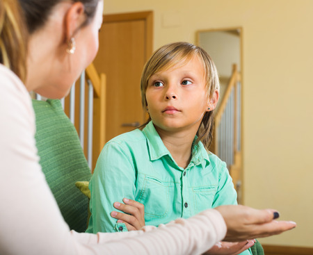 Serious mother scolding naughty teenage son in home interior  photo