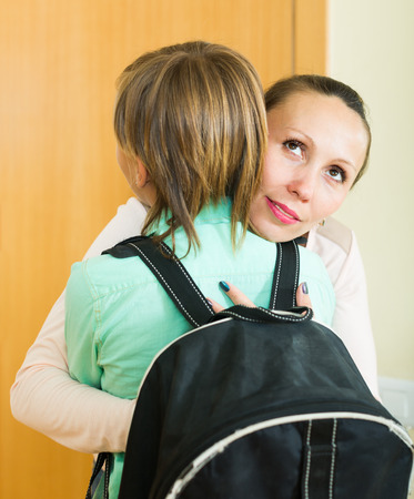 lecturing: Positive mature mother hugging and lecturing boy before he goes to school